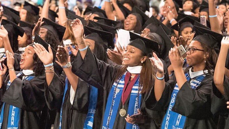 Group shot of Spelman College graduates cheering during graduation ceremony and wearing caps and gowns