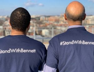 Two individuals wearing #StandWithBennett T-shirts