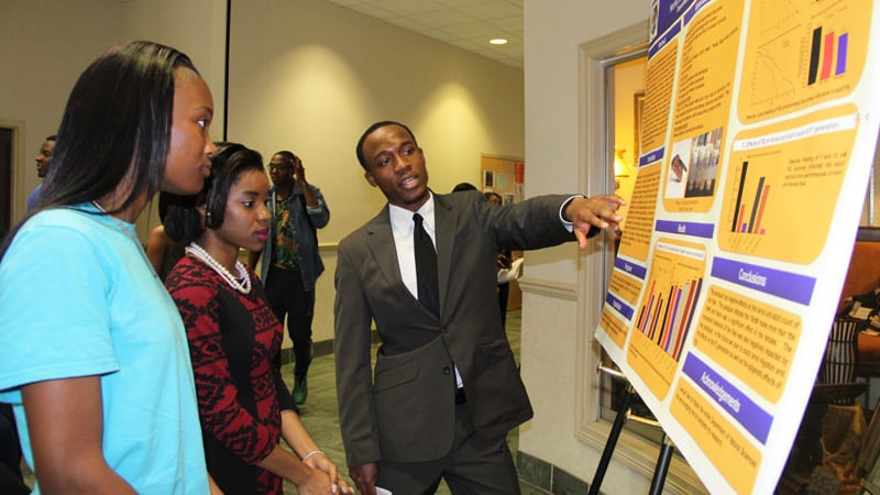 Students talking in front of statistical presentation board at Stillman College
