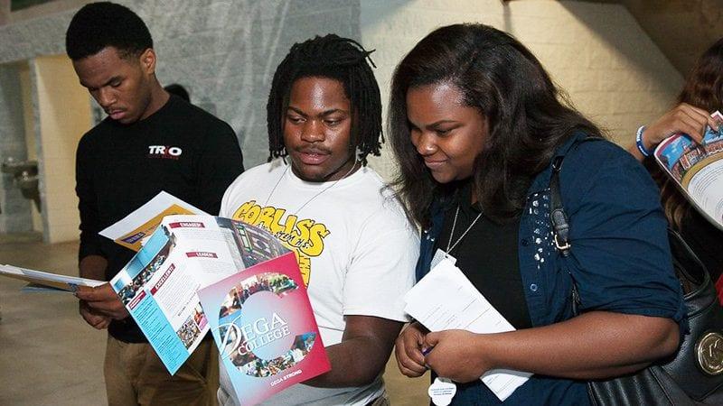 Headshot of students looking at brochures