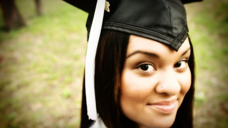 Headshot of female college graduate wearing cap and gown