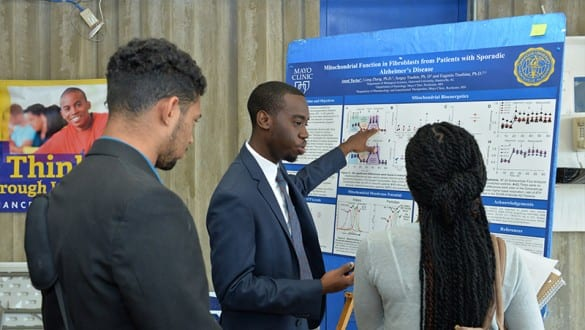 Three students discussing Alzheimer's disease in front of a presentation board