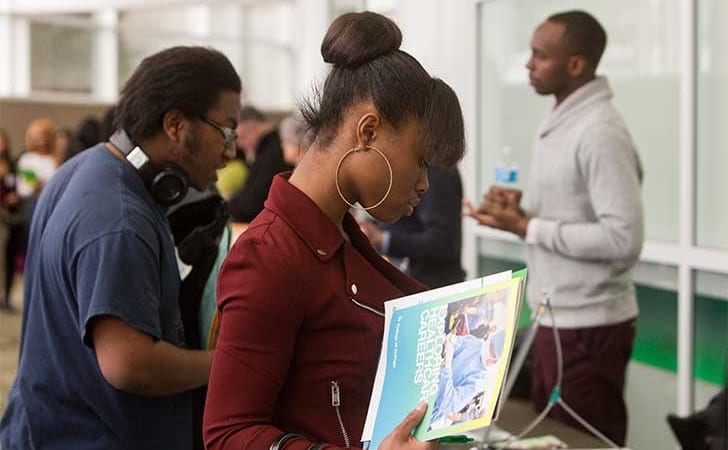 Group of students reading materials during a college career fair