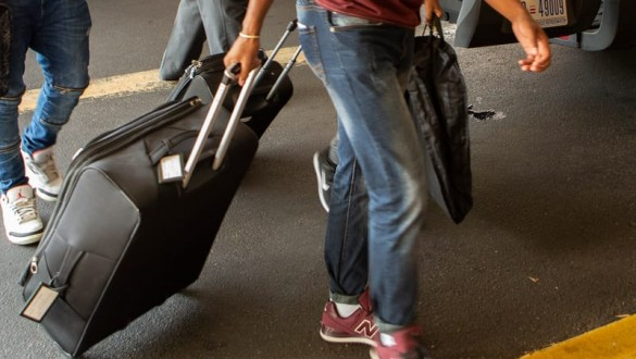 Suitcase being rolled through airport by man