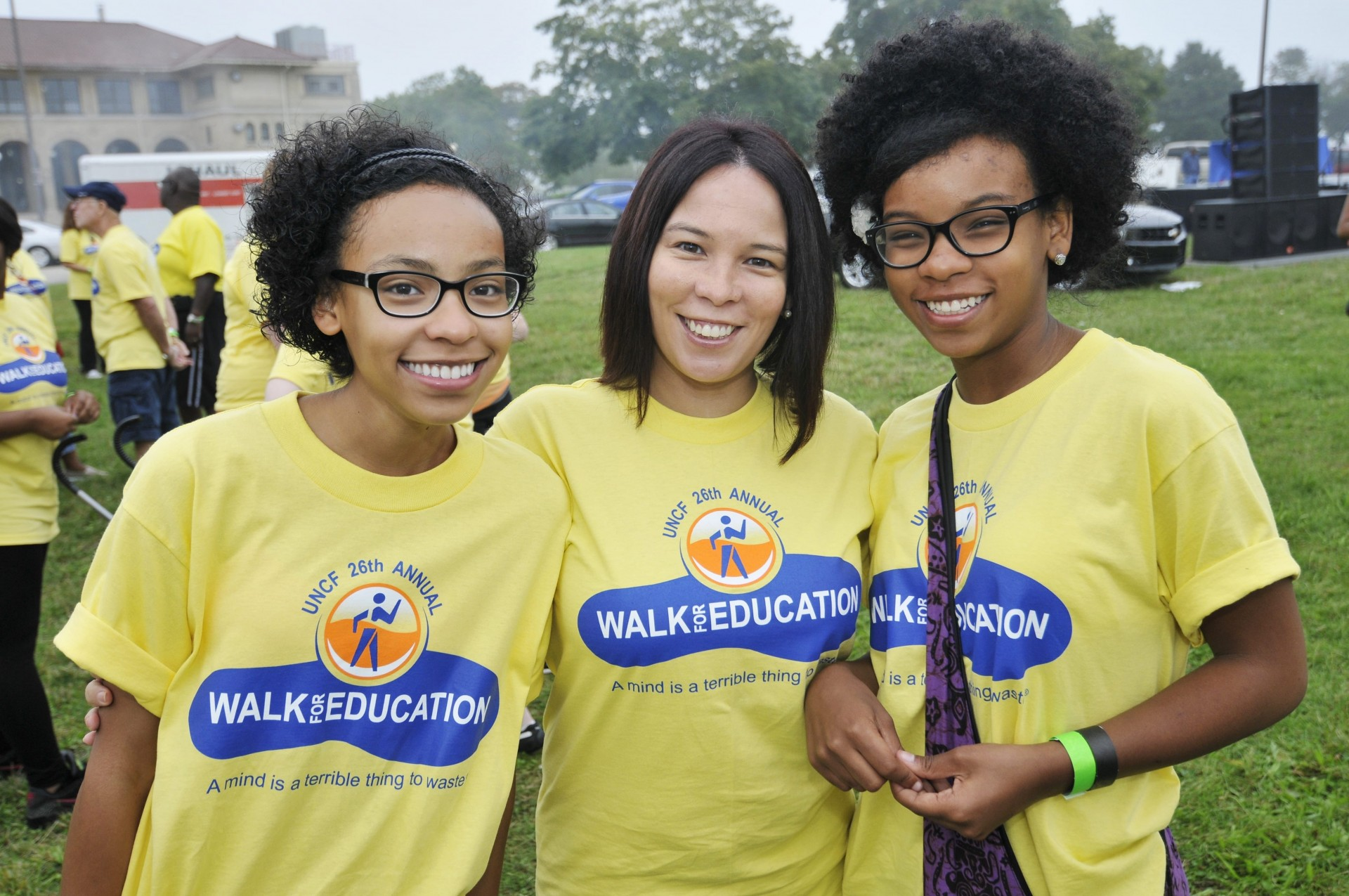 Three females wearing UNCF Walk t-shirts smiling
