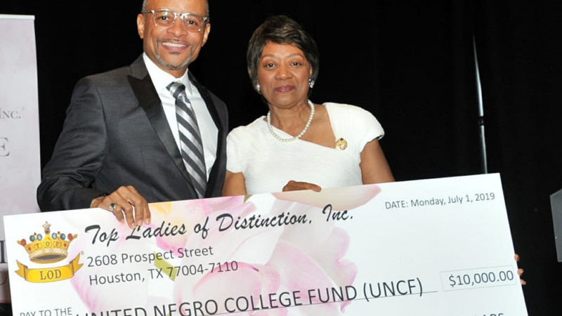 Two individuals presenting donation from Top Ladies of Distinction, Inc. to UNCF