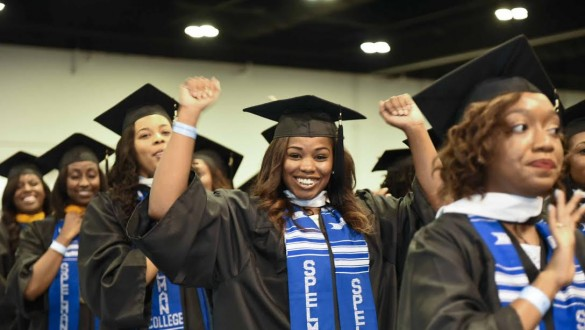 Spelman college graduates during graduation ceremony wearing caps and gowns and cheering