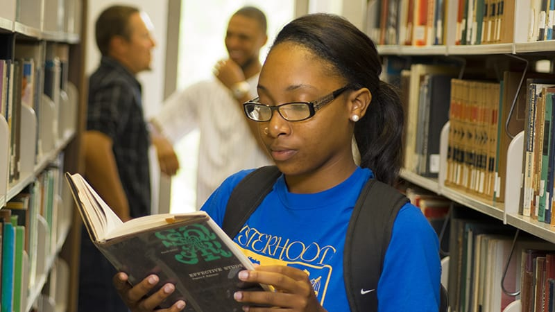 A female Voorhees student reads a book in the campus library