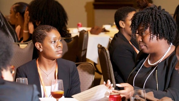 2 female Walton fellows conference attendees talking during group sessions