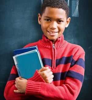 Male young elementary school student holding books